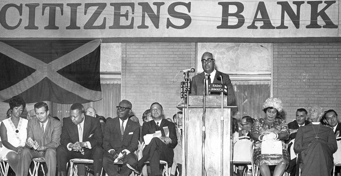 "Optimism: Launching Citizens Bank in 1968, Hon. Russell Graham, Custos of St. Andrew and Board Chairman of the bank speaks of its intention to ""try in every way to improve the economy"". Front row from left: Mrs. Seaga, the Hon. Edward Seaga, Minister of Finance and Planning, Prime Minister, the Hon. Hugh Shearer, Governor General, Sir Clifford Campbell, Mr. William F. Smith, a director of the Bank and master of ceremonies, Lady Campbell and the Anglican Bishop of Jamaica, the Rt. Rev. J. C. Swaby. © 1968 The Gleaner"