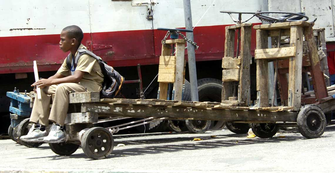 Schoolboy relaxes on one of the haulage carts chained together for safety at Coronation Market. © The Gleaner